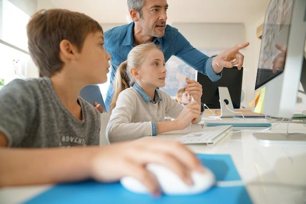 Professor com alunos em uma aula de informática Foto Premium