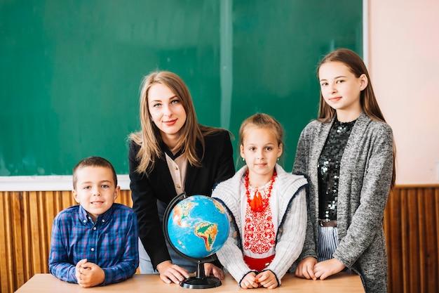 Professor da escola feminina e estudantes em pé com o globo Foto gratuita