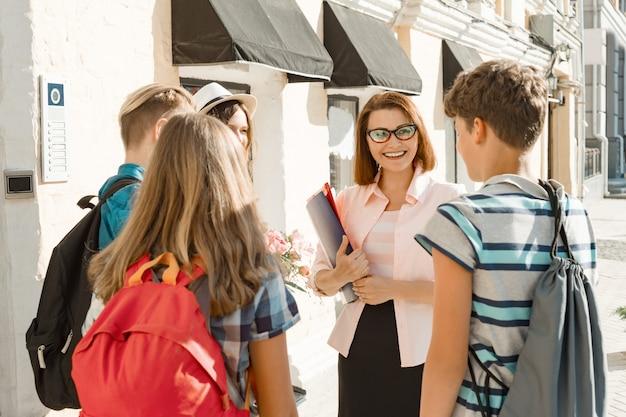 Professor de escola ao ar livre com grupo de adolescentes estudantes do ensino médio Foto Premium