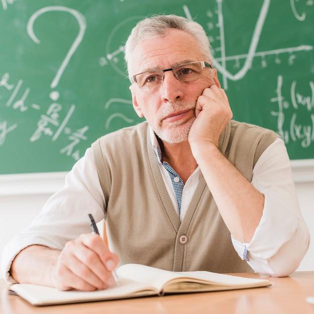 Professor de matemática envelhecido concentrado pensando na mesa Foto gratuita