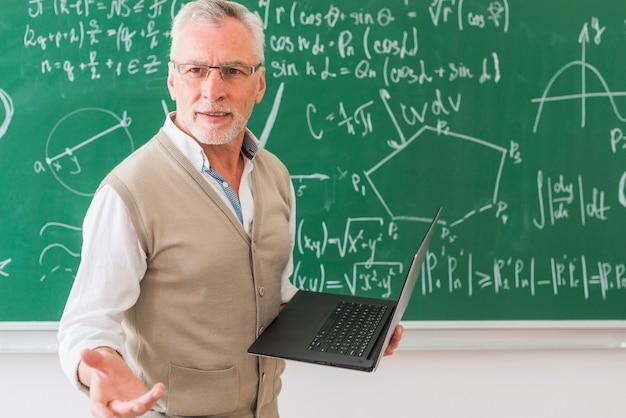 Professor de matemática envelhecido em pé com notebook Foto gratuita