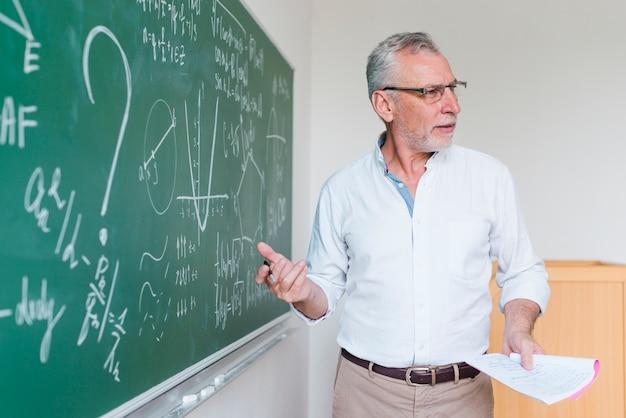 Professor de matemática envelhecido explicando a fórmula na sala de aula Foto gratuita