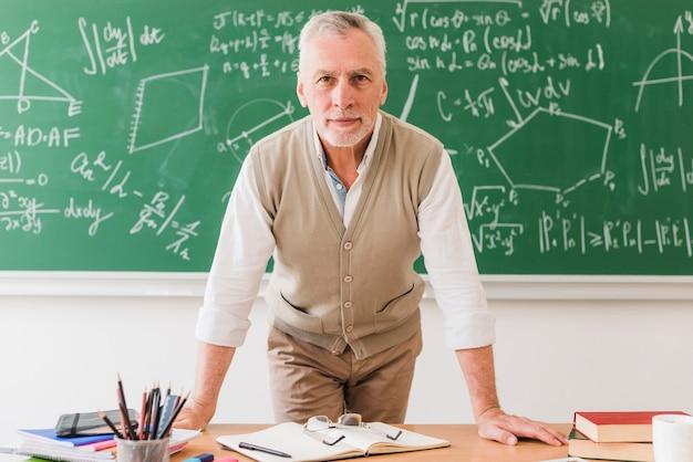 Professor de matemática envelhecido positivo, apoiando-se na mesa Foto gratuita