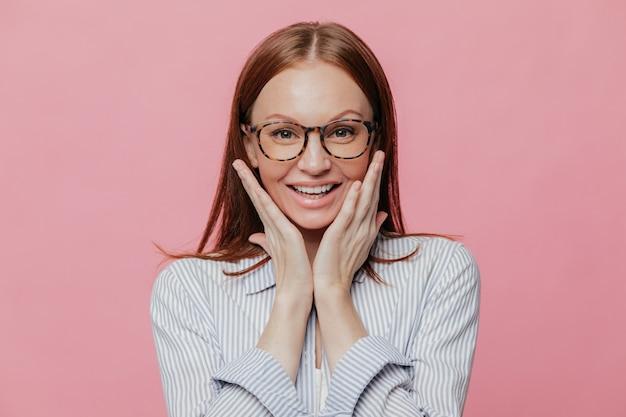 Professor de mulher jovem e atraente com sorriso, toca as bochechas Foto Premium