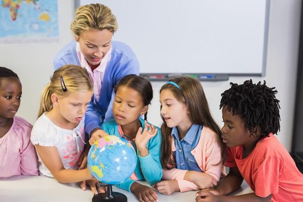 Professor discutindo globo com crianças Foto Premium