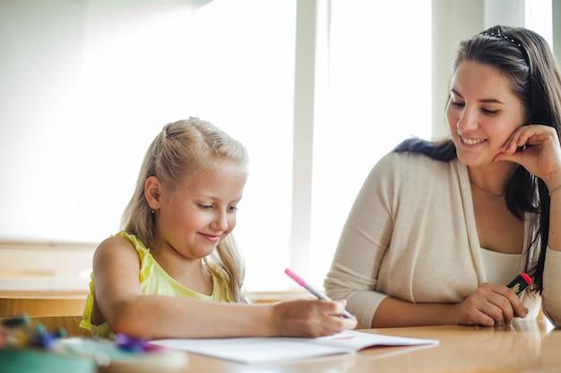 Professor e coleira sentada à mesa, sorrindo Foto gratuita