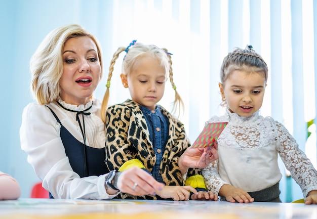 Professor e crianças brincando juntos com cartões coloridos. Foto Premium