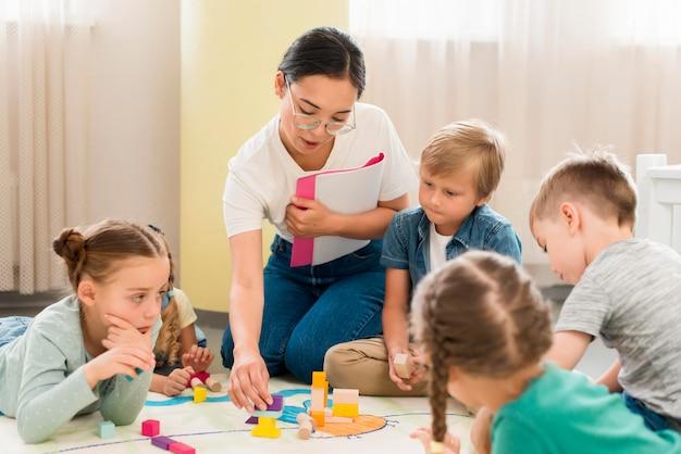 Professor e crianças dando aula dentro de casa Foto Premium