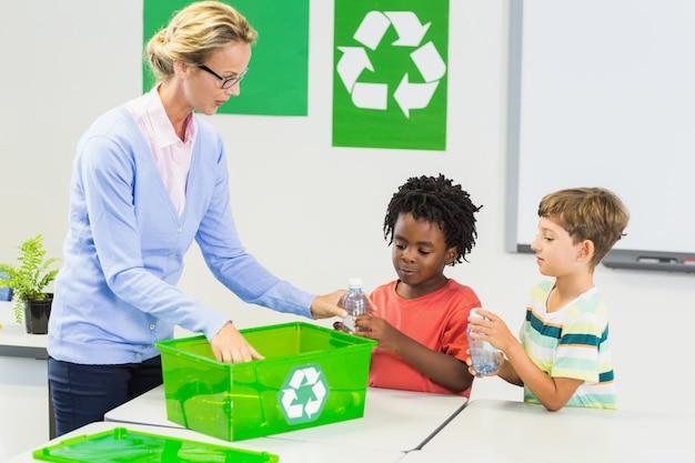 Professor e crianças discutindo sobre reciclar Foto Premium