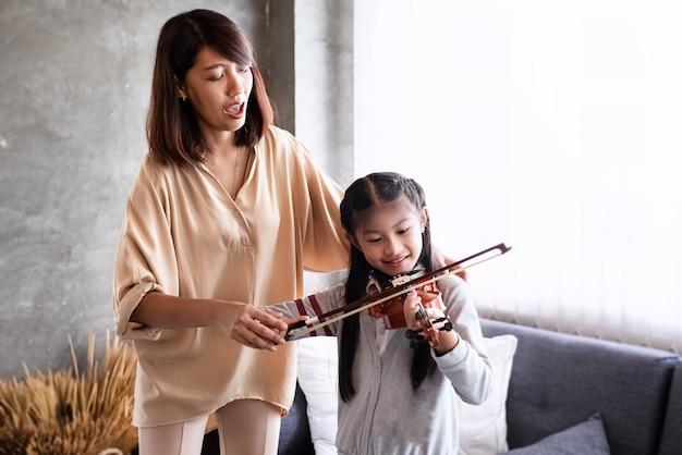 Professor ensinando menina para tocar violino Foto Premium