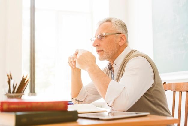 Professor envelhecido bebendo em sala de aula Foto gratuita