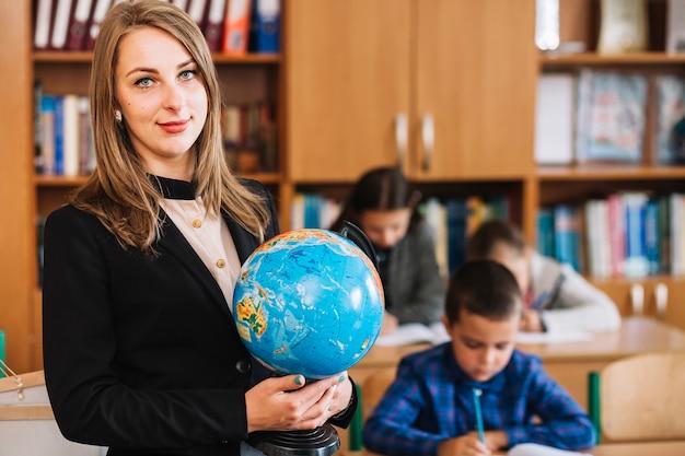 Professor escolar, com, globo, experiência, de, estudar, pupilas Foto gratuita