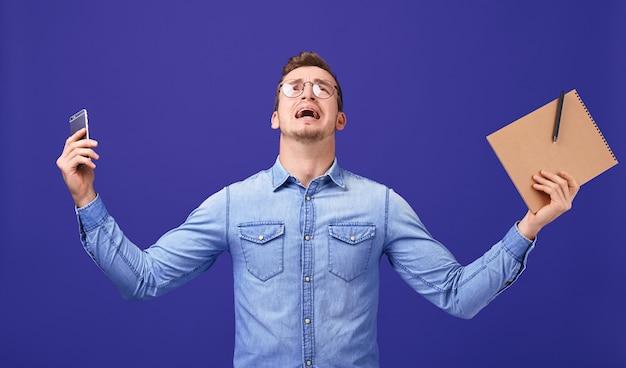 Professor ferido com as mãos para cima em copos, camisa jeans azul gritando Foto Premium
