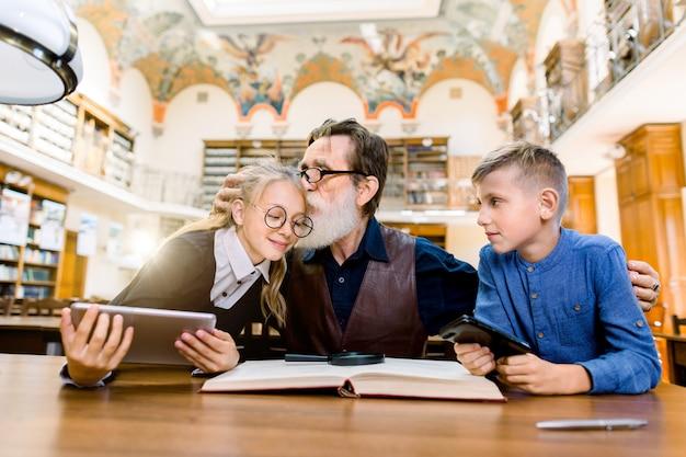 Professor homem idoso e seus alunos adolescentes, menino e menina, sentado à mesa na biblioteca Foto Premium