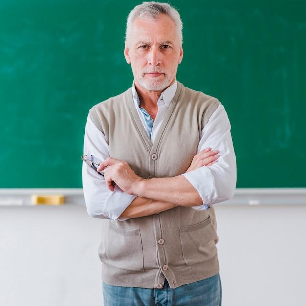 Professor masculino sênior, com, braços cruzaram, ficar, contra, chalkboard Foto gratuita