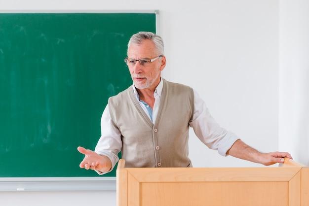 Professor masculino sênior, explicando a lição perto de lousa Foto gratuita