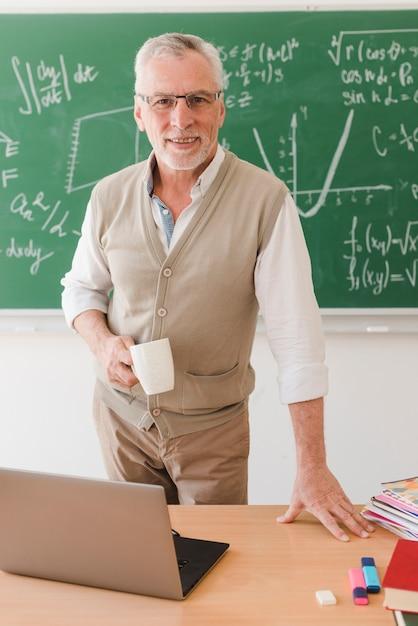 Professor sênior, estar, escrivaninha, em, sala aula Foto gratuita