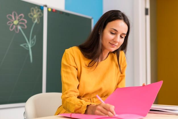 Professor sorridente fazendo anotações Foto gratuita