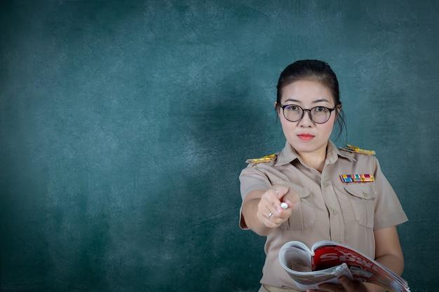 Professor tailandês irritado com roupa oficial em pé na frente do encosto, apontando o dedo para a câmera Foto gratuita