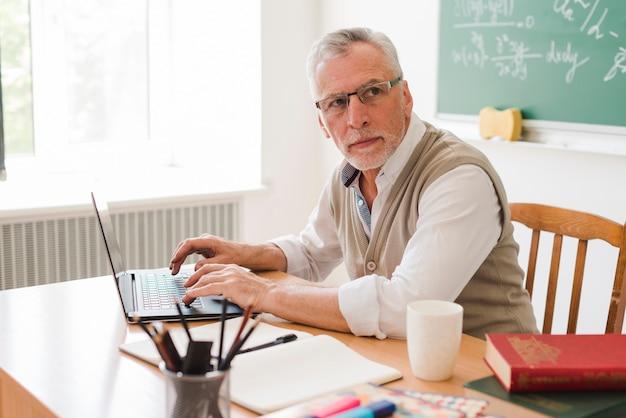 Professor velho inteligente usando laptop em sala de aula Foto gratuita