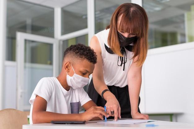 Professora ajudando seu aluno enquanto usava máscaras médicas Foto gratuita