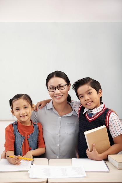 Professora asiática em copos posando em sala de aula com alunos de menino e menina Foto gratuita