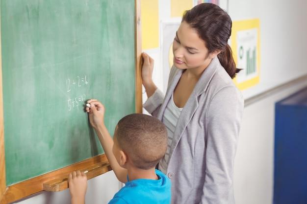 Professora bonita, ajudando o aluno na lousa Foto Premium