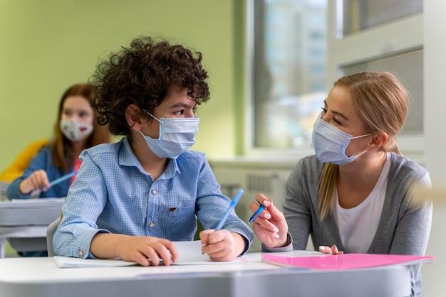 Professora com máscara médica ajudando alunos em sala de aula Foto gratuita