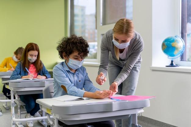 Professora com máscara médica dando desinfetante para as mãos para crianças na sala de aula Foto gratuita