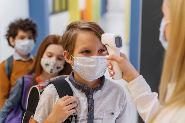 Professora com máscara médica verificando a temperatura do aluno na escola Foto gratuita