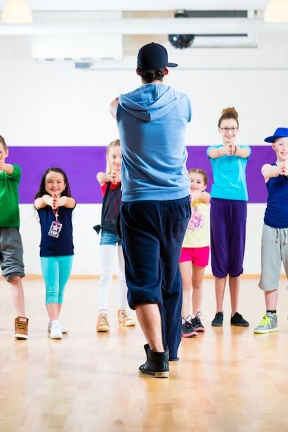 Professora de dança dando aula de fitness para crianças zumba Foto Premium