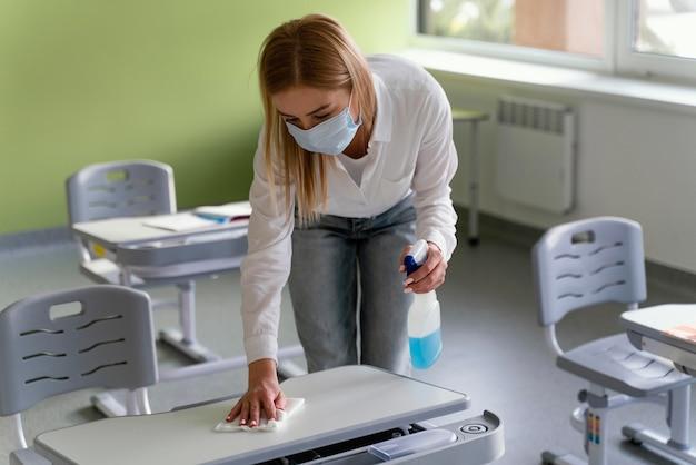 Professora desinfetando bancos escolares em sala de aula Foto gratuita