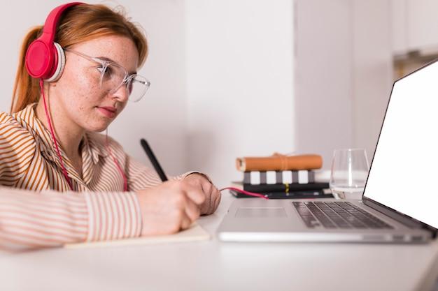 Professora em casa dando aula online usando laptop Foto Premium