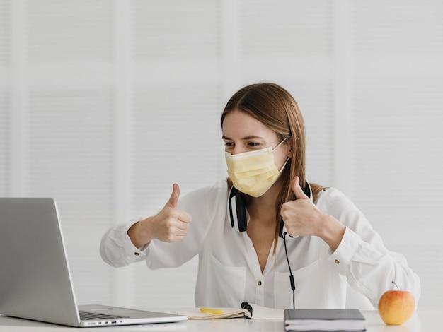 Professora frequentando seu curso online e usando máscara médica Foto gratuita