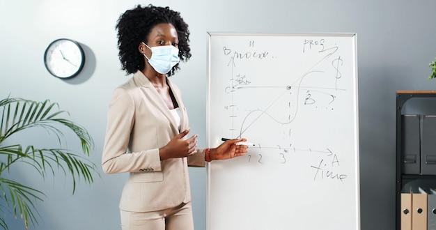 Professora jovem afro-americana na máscara médica em pé na diretoria na sala de aula e dizendo as leis da física ou geometria para a aula. conceito de pandemia. escola durante o coronavírus. aula educativa. Foto Premium