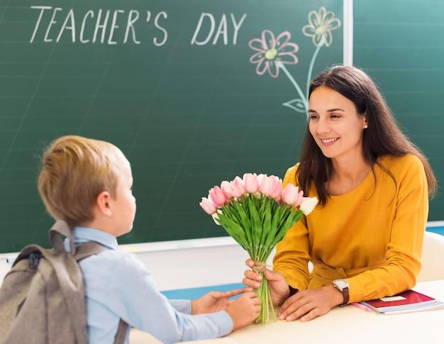 Professora recebendo flores de seus alunos Foto Premium