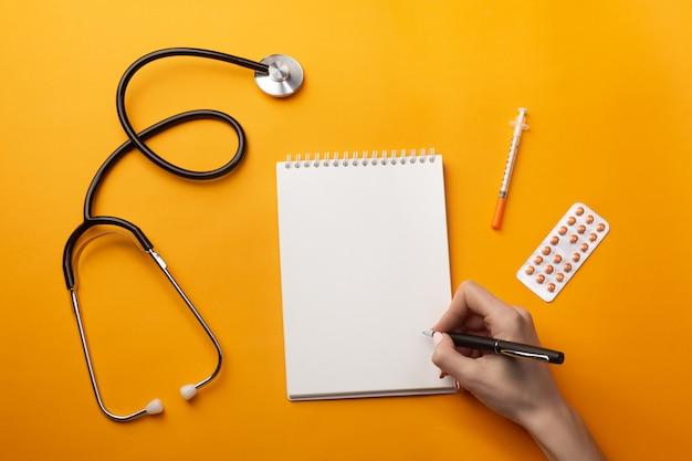 Profissional, doutor, escrita, registros médicos, em, um, caderno, com, estetoscópio, siringa, e, pílulas Foto Premium