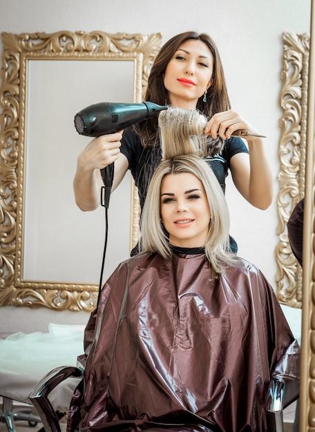 Profissional estilista, cabeleireiro fazendo penteado para o cliente com um secador de cabelo Foto Premium