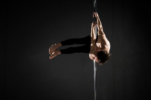 Profissional jovem masculino modelo pole dancing Foto gratuita