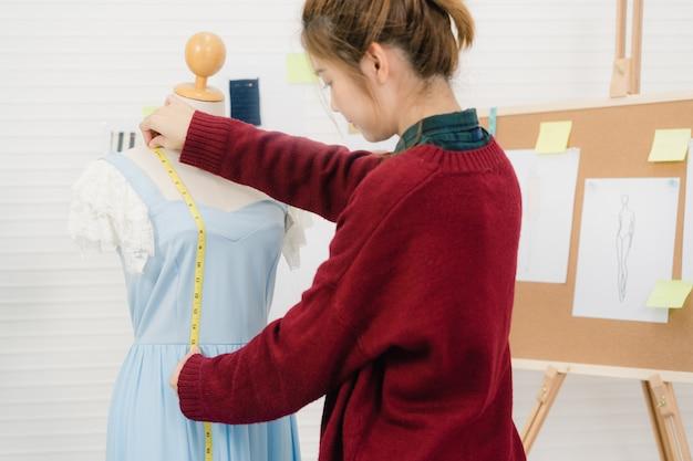 Profissional linda asiática feminino designer de moda trabalhando vestido de medição em uma roupa de manequim Foto gratuita