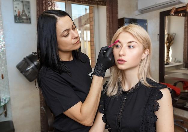 Profissional maquiagem artista sobrancelha tingimento com pincel no salão de beleza de garota atraente. Foto Premium