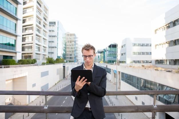 Profissional sério focado trabalhando em tablet Foto gratuita