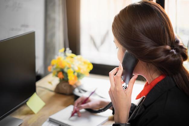 Programação da nota da mulher de negócio no livro e fala com o cliente pelo telefone. Foto Premium