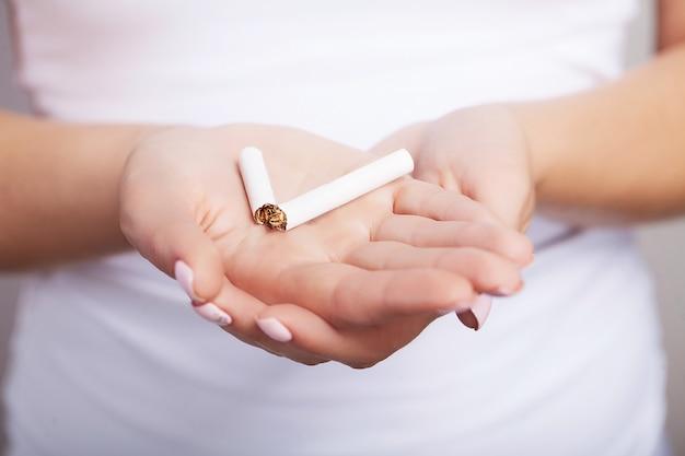Proibido fumar. sorrindo, a garota corta um cigarro. não fume com problemas que dependam da nicotina. Foto Premium