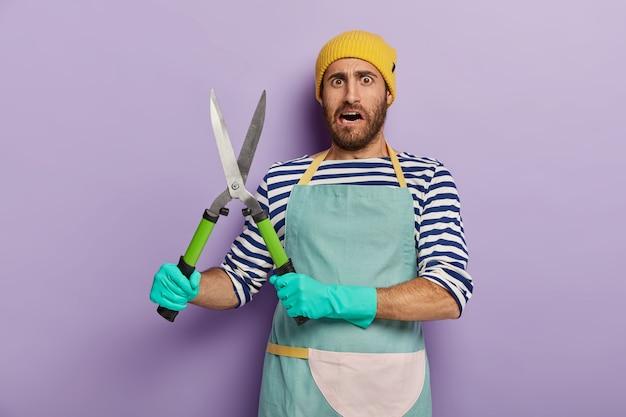 Projetista ou jardineiro insatisfeito segura tesouras de jardinagem, vai cortar arbustos verdes e usa chapéu amarelo Foto gratuita