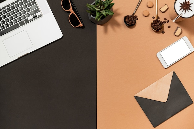 Projeto do café da área de trabalho plano com dispositivo digital e envelope de papel fechado. aroma arábica feijão, laptop, celular, óculos de sol, vista superior da planta. Foto Premium
