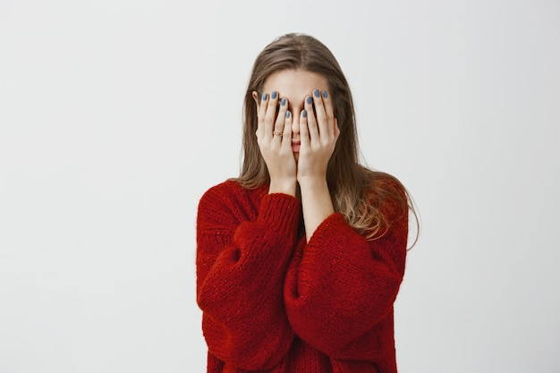 Promessa, não estou espiando. foto de mulher atraente cansada e cansada de suéter vermelho solto, cobrindo o rosto com as palmas das mãos, sentindo-se estressada e exausta, tendo necessidade de relaxar e dormir sobre a parede cinza Foto gratuita
