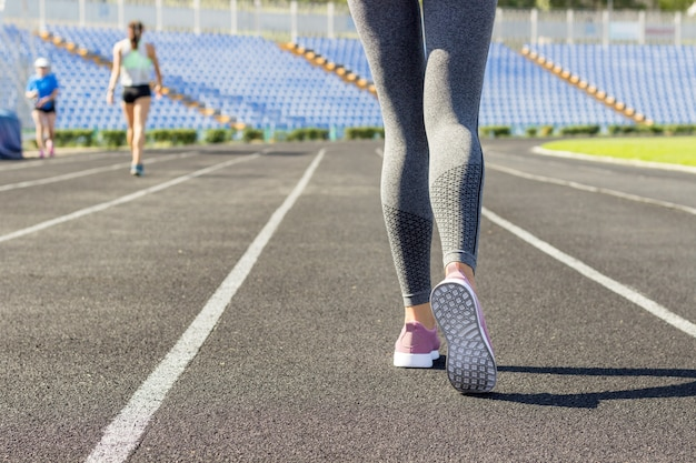 Pronto para ir. feche a foto do sapato de atleta feminina na linha de partida. menina na pista do estádio, preparando-se para uma corrida. esportes e conceito saudável Foto Premium