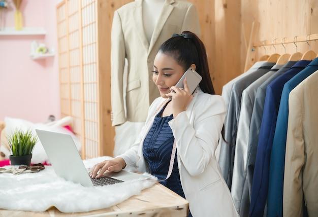 Proprietário da empresa mulher trabalhando em sua loja de alfaiate Foto gratuita