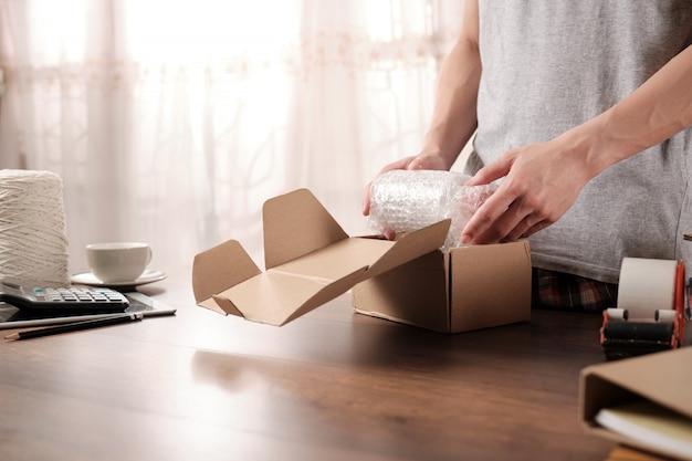 Proprietário de empresa de inicialização jovem embalagem de produtos em plástico à prova de choque para enviado ao cliente Foto Premium